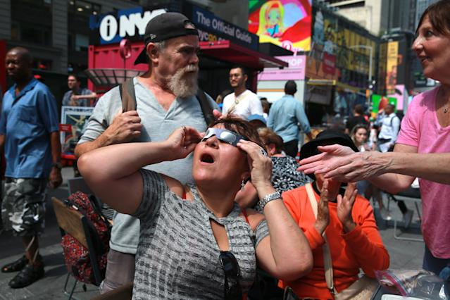 <p>A woman looks overjoyed as she watches the total solar eclipse in Times Square, New York City, on Aug. 21, 2017. (Gordon Donovan/Yahoo News) </p>