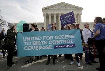 FILE PHOTO: Supporters of contraception rally before Zubik v. Burwell, an appeal brought by Christian groups demanding full exemption from the requirement to provide insurance covering contraception under the Affordable Care Act, is heard by the U.S. Supreme Court in Washington March 23, 2016.      REUTERS/Joshua Roberts/File Photo
