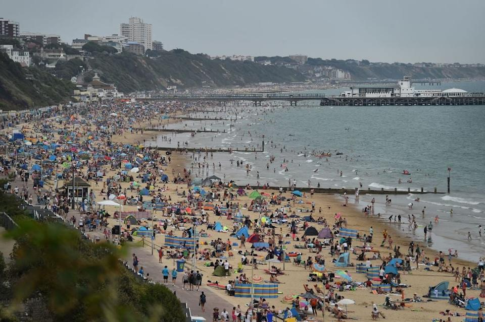 Beachgoers enjoy the sunshine as they sunbathe and play in the sea on Bournemouth beach: Getty Images