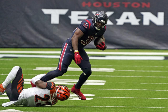 Houston Texans running back David Johnson (31) runs for a first down as Cincinnati Bengals cornerback Darius Phillips (23) reaches to tackle him during the second half of an NFL football game Sunday, Dec. 27, 2020, in Houston. (AP Photo/Sam Craft)