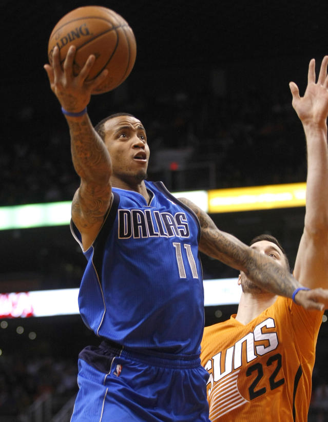 Dallas Mavericks shooting guard Monta Ellis (11) drives and scores against Phoenix Suns center Miles Plumlee (22) in the second quarter during an NBA basketball game on Friday, Jan. 17, 2014, in Phoenix. (AP Photo/Rick Scuteri)