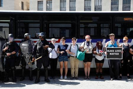 Police disembark from a bus as protesters lock arms preventing the bus from moving during a standoff with protesters after the not guilty verdict of Jason Stockley, a former St. Louis police officer charged with the 2011 shooting of Anthony Lamar Smith, on Tucker Blvd in downtown St.Louis, Missouri. REUTERS/Whitney Curtis
