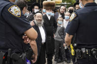 Members of the Orthodox Jewish community speak with NYPD officers on a street corner, Wednesday, Oct. 7, 2020, in the Borough Park neighborhood of the Brooklyn borough of New York. Gov. Andrew Cuomo moved to reinstate restrictions on businesses, houses of worship and schools in and near areas where coronavirus cases are spiking. Many neighborhoods that stand to be affected are home to large enclaves of Orthodox Jews. (AP Photo/John Minchillo)