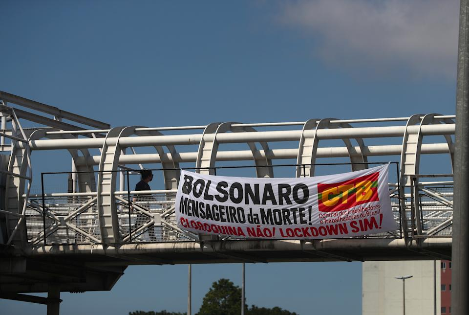 """A banner reading """"Bolsonaro messenger of Death! Cloroquina no, lockdown yes!"""" hangs from a bridge, as the spread of the coronavirus disease (COVID-19) continues, in Rio de Janeiro, Brazil, May 25, 2020. REUTERS/Pilar Olivares"""
