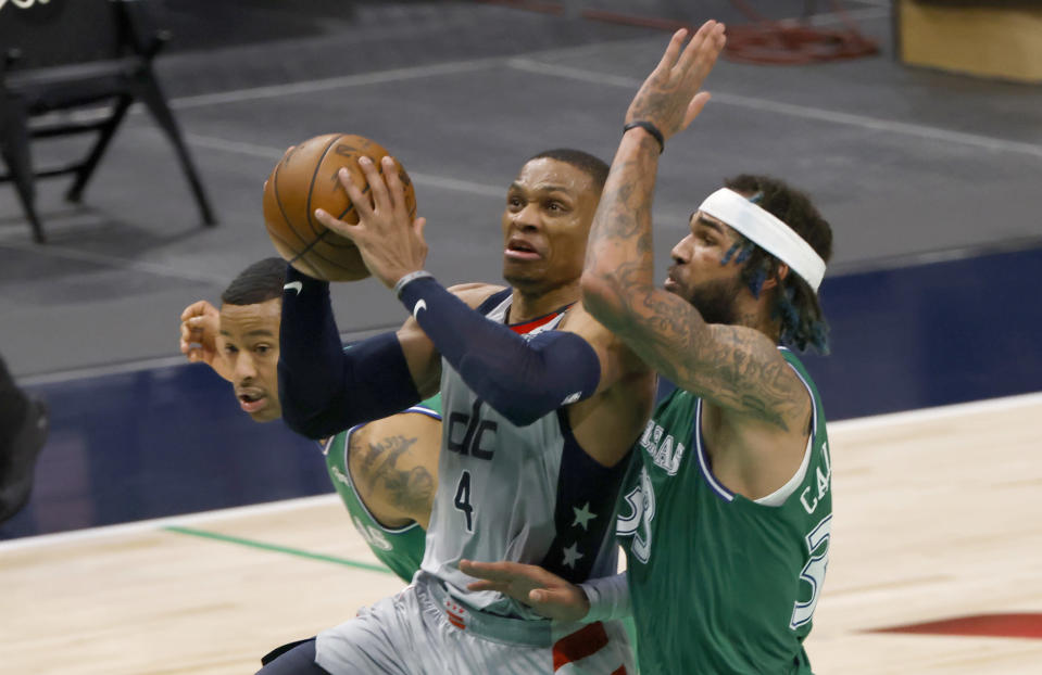 Washington Wizards guard Russell Westbrook (4) drives inside as Dallas Mavericks guard Trey Burke (3) and center Willie Cauley-Stein (33) defend during the second half of an NBA basketball game Saturday, May 1, 2021, in Dallas. (AP Photo/Ron Jenkins)