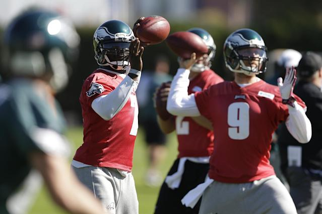 Philadelphia Eagles quarterbacks Michael Vick (7) and Nick Foles (9) throws passes during practice at the NFL football team's training facility, Tuesday, Oct. 15, 2013, in Philadelphia. (AP Photo/Matt Rourke)
