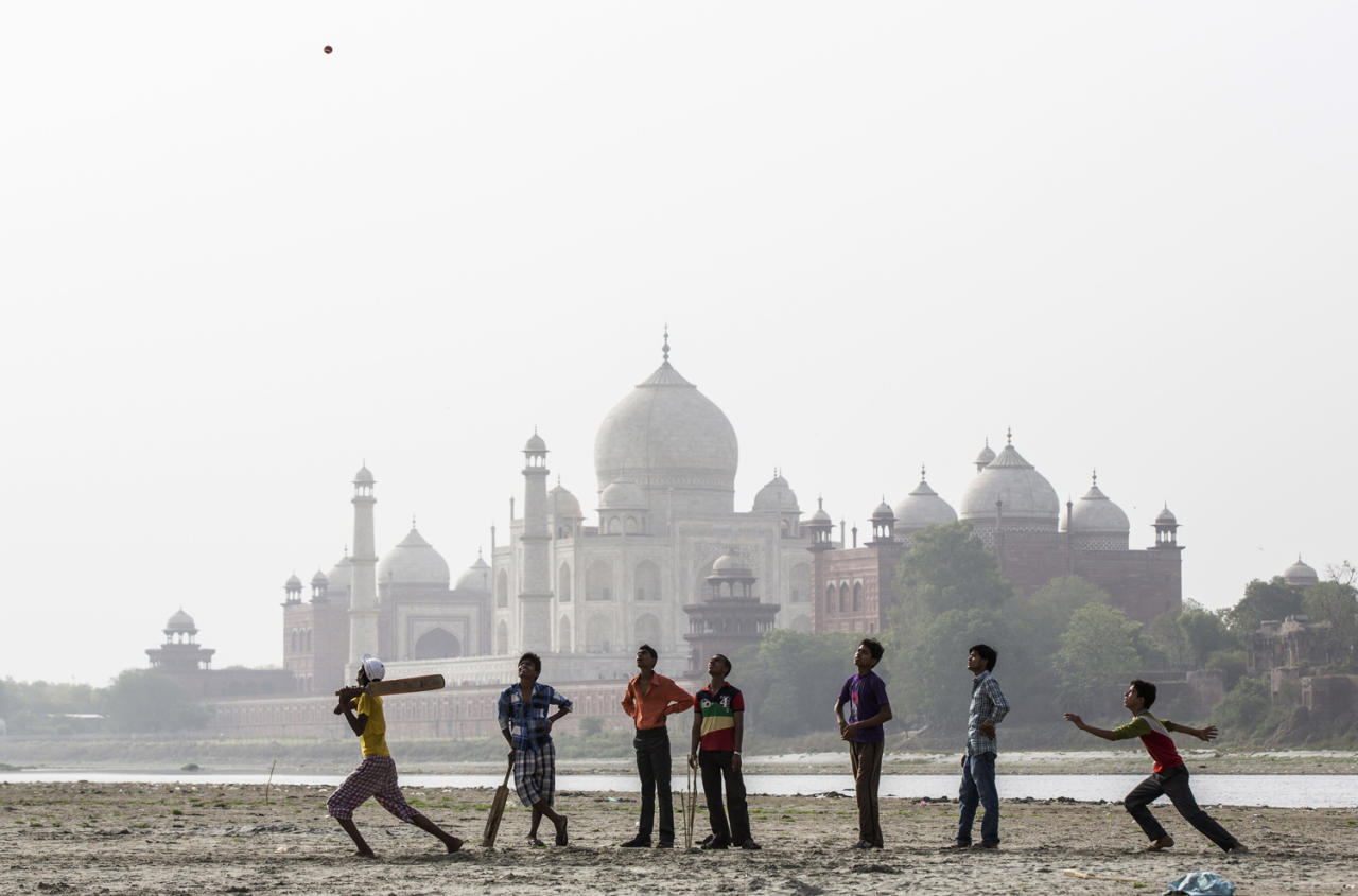 AGRA, INDIA - MAY 28: Indian boys play cricket on the banks of the Yamuna river as the Taj Mahal is seen in the distance on May 28, 2013 in Agra, India. Completed in 1643, the mausoleum was built by the Mughal emperor Shah Jahan in memory of his third wife, Mumtaz Mahal, who is buried there alongside Jahan.(Photo by Daniel Berehulak/Getty Images)