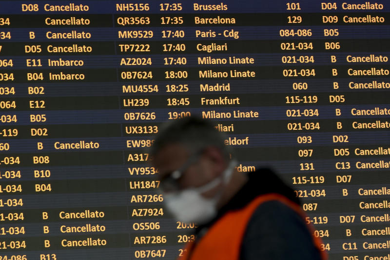 A man wearing a mask walk past a departures monitor at the Rome Leonardo da Vinci international airport, Thursday, March 12, 2020. Italians woke up to yet further virus-containment restrictions after Premier Giuseppe Conte ordered restaurants, cafes and retail shops closed after imposing a nationwide lockdown on personal movement. For most people, the new coronavirus causes only mild or moderate symptoms, such as fever and cough. For some, especially older adults and people with existing health problems, it can cause more severe illness, including pneumonia. (AP Photo/Andrew Medichini)