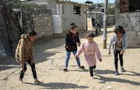 Palestinian girls gather in a street in the Khan Yunis camp for Palestinian refugees in the southern Gaza Strip in February 2021