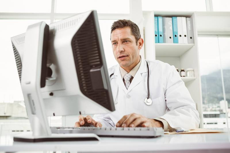 Male doctor working at a desktop computer with a stethoscope hanging on his shoulders.
