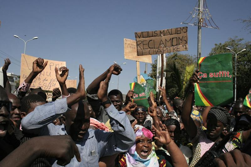 FILE - In this Dec. 8, 2012, file photo, Malians demonstrate in favor of an international military intervention to regain control of the country's Islamist-controlled north, in Bamako, Mali. They carry signs that say 'That's enough, let the government work' right, and 'We Malians Demand Chapter 7,' center, referring to the chapter of the United Nations Charter which would be used to authorize international military intervention. The Pentagon is moving toward setting up a military base in northwest Africa from which to operate surveillance drones to collect intelligence on Islamic militants in the region, several U.S. defense officials said Tuesday, Jan. 29, 2013. The officials, speaking on condition of anonymity because the plan is still in the works, said the base in Niger would position the U.S. to provide more help to French troops fighting al-Qaida-backed militants in neighboring Mali. (AP Photo/Harouna Traore)