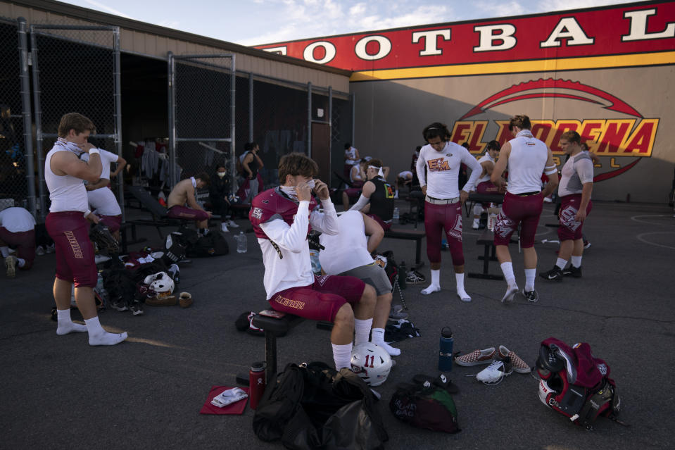 El Modena tight end Tom Leonard, center, and teammates put on their gear outdoors due to COVID-19 restrictions before the team's high school football game with El Dorado in Orange, Calif., Friday, March 19, 2021. The team recently played its first football game in a year as more California counties ease coronavirus restrictions and life in the nation's most populous state inches back to normalcy. (AP Photo/Jae C. Hong)