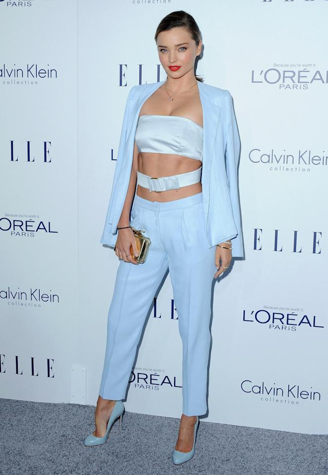 <p>Wearing trousers to a fancy event is so working girl and model Miranda Kerr is not that. She spends hours at the gym on a daily basis so she paired the pants with a silk bandeau and drew attention to her abs with a belt wrapped around her six pack abs. She draped a blazer over her shoulders to cover up a little and painted her lips red for just a little color variation.  </p>