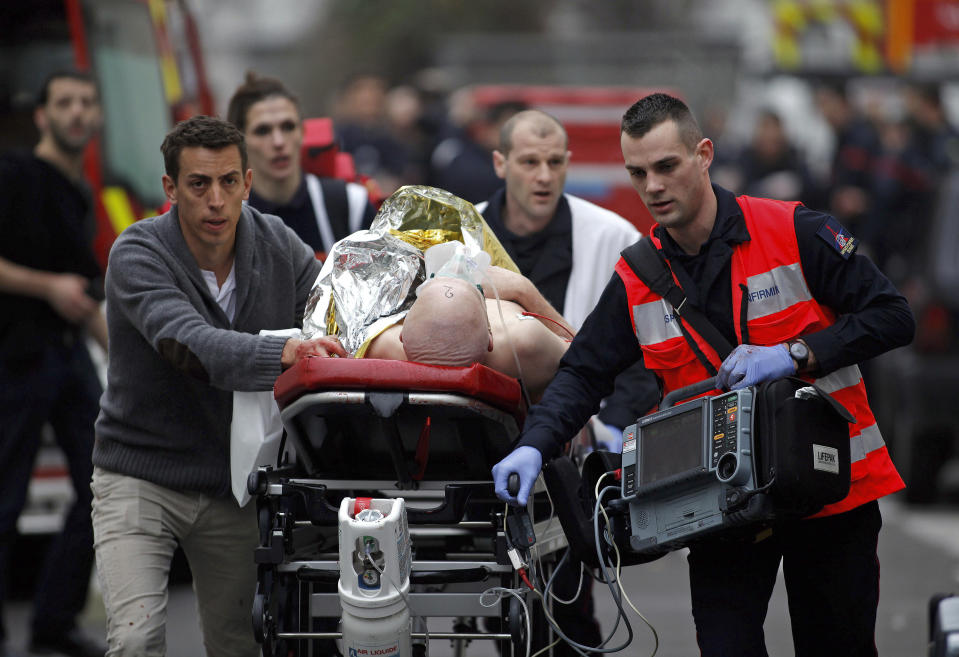 FILE – In this Wednesday, Jan. 7, 2014, file photo an injured person is evacuated outside the French satirical magazine Charlie Hebdo's office, in Paris. In the 20 years since the Sept. 11, 2001 terrorist attacks in the United States, a mixture of homegrown extremists, geography and weaknesses in counterterrorism strategies have combined to turn Europe into a prime target for jihadists bent on hurting the West. (AP Photo/Thibault Camus, File)