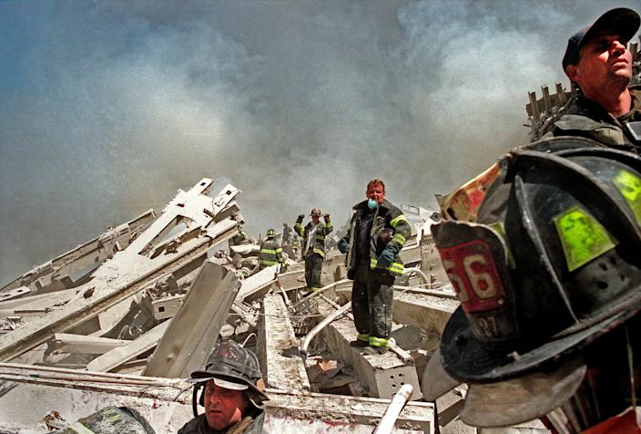 Firefighters are seen on the rubble.