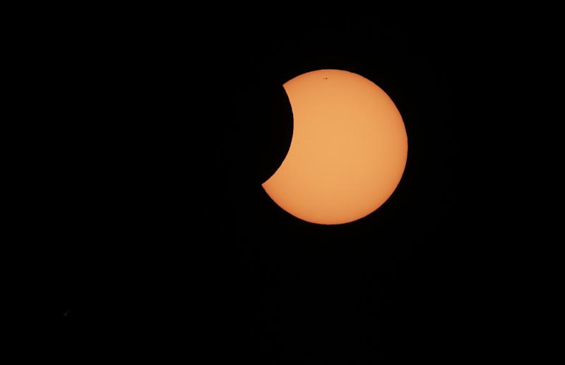 The moon begins to cross in front of the sun during a partial solar eclipse in Sydney, Friday, May 10, 2013. At remote outposts across Australia, scientists and spectators gathered to watch as the eclipse castes its approximately 200-kilometer-wide (120-mile-wide) shadow at dawn over Western Australia, before moving east through the Northern Territory and the top of Queensland state.(AP Photo/Rick Rycroft)