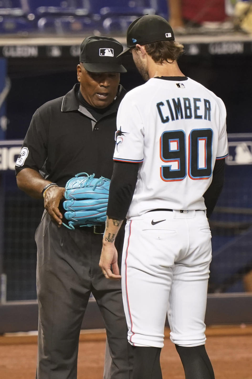 MLB umpire Laz Diaz checks the glove of Miami Marlins relief pitcher Adam Cimber (90) during the sixth inning of a baseball game against the Toronto Blue Jays, Wednesday, June 23, 2021, in Miami. (AP Photo/Marta Lavandier)