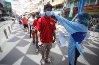 A health worker checks the temperature of a man falling in line for a COVID-19 swab test in Khaosan Road in Bangkok, Thailand Wednesday, April 14, 2021. Thailand recorded more than 1,000 COVID-19 infections on Wednesday, setting a daily record and adding pressure on the government to do more to control the country's spiking transmission rates. (AP Photo/Somchai Chanjirakitti)
