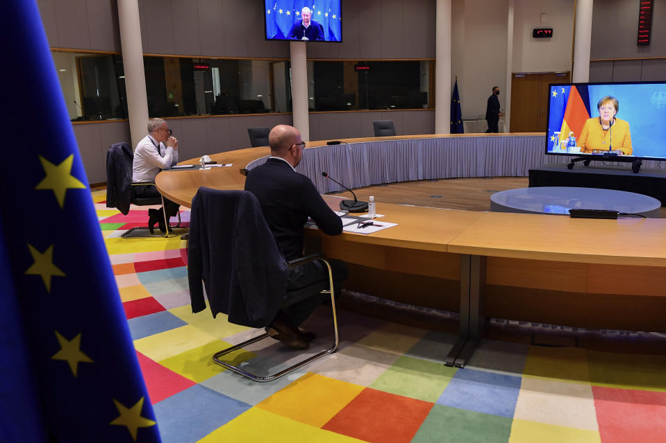 European Council President Charles Michel participates in a video conference with German Chancellor Angela Merkel, on screen, at the European Council building in Brussels, Friday, March 5, 2021. (John Thys, Pool via AP)