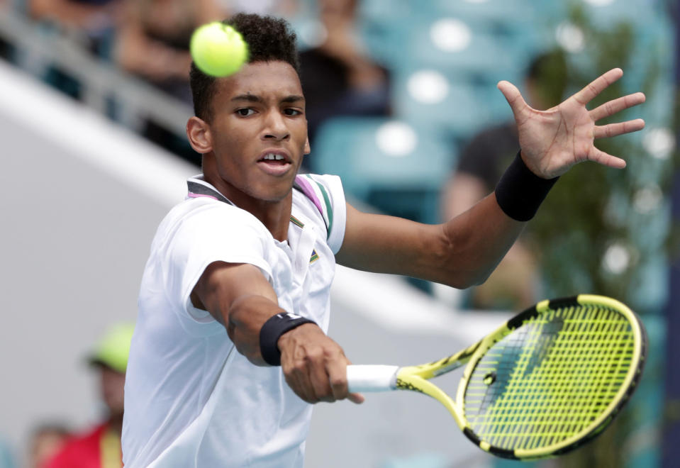 Felix Auger-Aliassime, of Canada, returns to John Isner during their semifinal match at the Miami Open tennis tournament, Friday, March 29, 2019, in Miami Gardens, Fla. (AP Photo/Lynne Sladky)