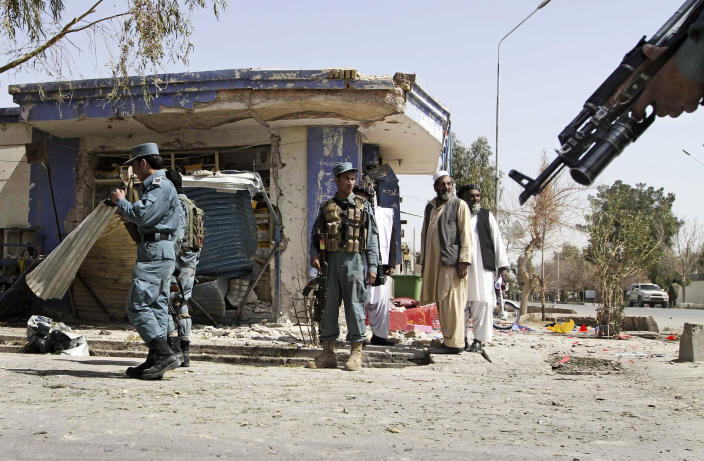 Afghan policemen are seen at the scene of a bomb explosion in Kandahar south of Kabul, Afghanistan, Wednesday, March 14, 2012. A delegation investigating Sunday's shooting killing civilians in Panjwai, Kandahar by a U.S. soldier was meeting in the southern city of Kandahar on Wednesday when a bomb hidden in a motorcycle exploded about 600 yards away. The blast killed one Afghan intelligence official and wounded three other people, but the delegation members were unharmed. (AP Photo/Allauddin khan)