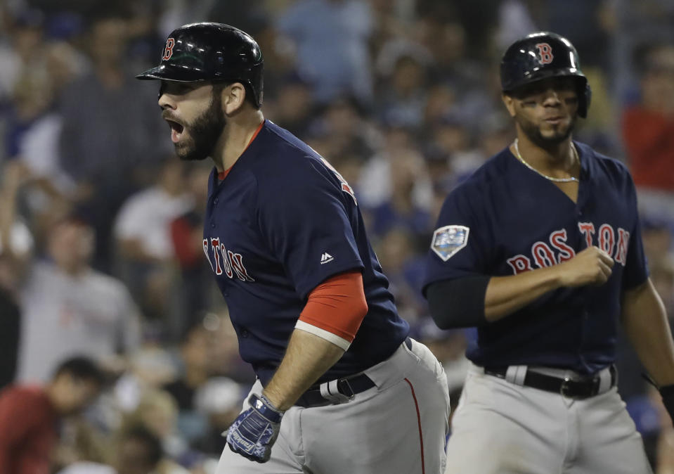 Boston Red Sox's Mitch Moreland celebrates his three-run home run during the seventh inning in Game 4 of the World Series baseball game against the Los Angeles Dodgers on Saturday, Oct. 27, 2018, in Los Angeles. At right is Boston Red Sox's Xander Bogaerts. (AP Photo/David J. Phillip)