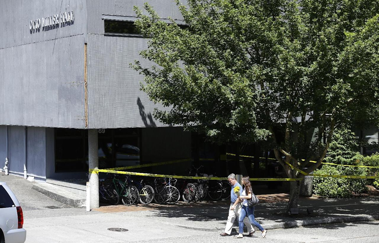 A woman carries flowers past police tape blocking the entrance to Otto Miller Hall at Seattle Pacific University on Friday, June 6, 2014 in Seattle, where a shooting took place Thursday afternoon. (AP Photo/Ted S. Warren)