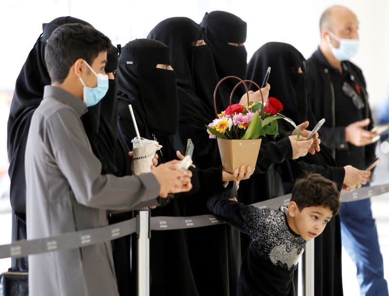 People wait to welcome their relatives who arrived from Doha, at King Khalid International Airport in Riyadh