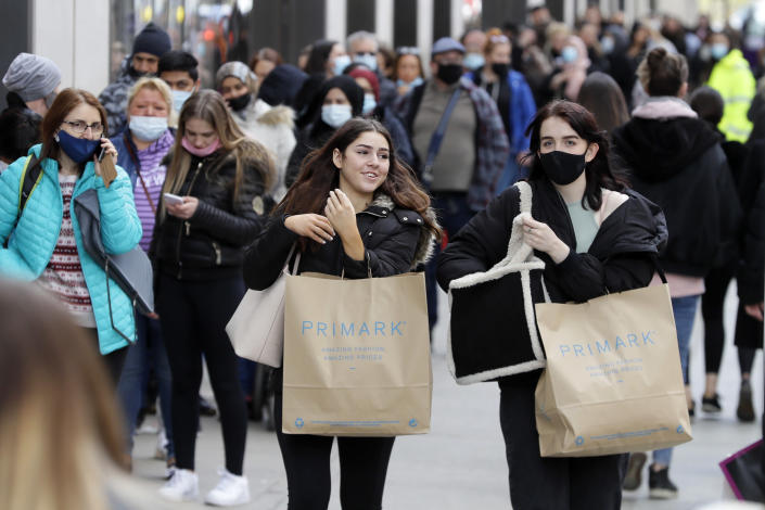 FILE - In this Monday, April 12, 2021 file photo, people carry shopping bags while others queue to enter a store on Oxford Street in London. British Prime Minister Boris Johnson is expected to confirm Monday June 14, 2021, that the next planned relaxation of coronavirus restrictions in England will be delayed as a result of the spread of the delta variant first identified in India. (AP Photo/Kirsty Wigglesworth, File)