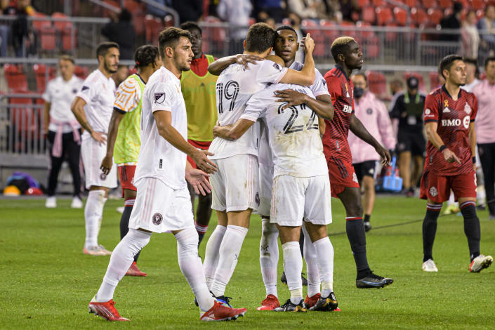 Inter Miami forward Federico Higuain (22), forward Robbie Robinson (19) and defender Christian Makoun celebrate after the team's win over Toronto FC in an MLS soccer match Tuesday, Sept. 14, 2021, in Toronto. (Christopher Katsarov/The Canadian Press via AP)