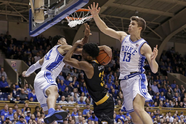 Winthrop forward Chase Claxton, center, drives to the basket against Duke guard Jordan Goldwire, left, and forward Joey Baker (13) during the first half of an NCAA college basketball game in Durham, N.C., Friday, Nov. 29, 2019. (AP Photo/Gerry Broome)