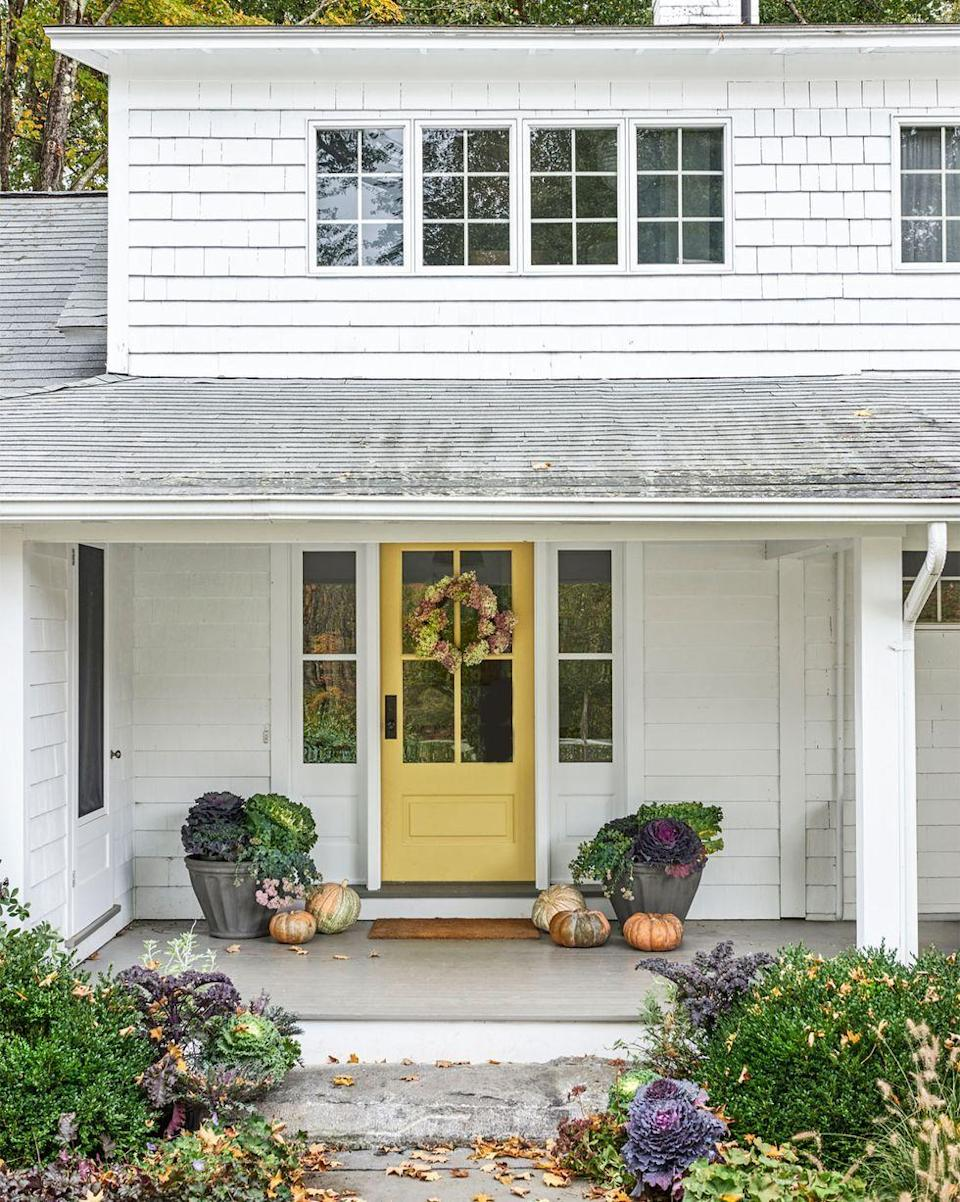 <p>A wreath of dried flowers hang on this happy gold front door. Pumpkins and cabbages on either side make for an effortless fall look.</p>