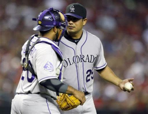 Colorado Rockies pitcher Jorge De La Rosa, right, talks with Wilin Rosario,left, in the fifth inning during a baseball game against the Arizona Diamondbacks on Friday, July 5, 2013, in Phoenix. (AP Photo/Rick Scuteri)