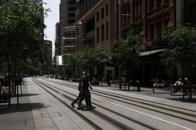 A person in a protective face mask crosses a street in Sydney