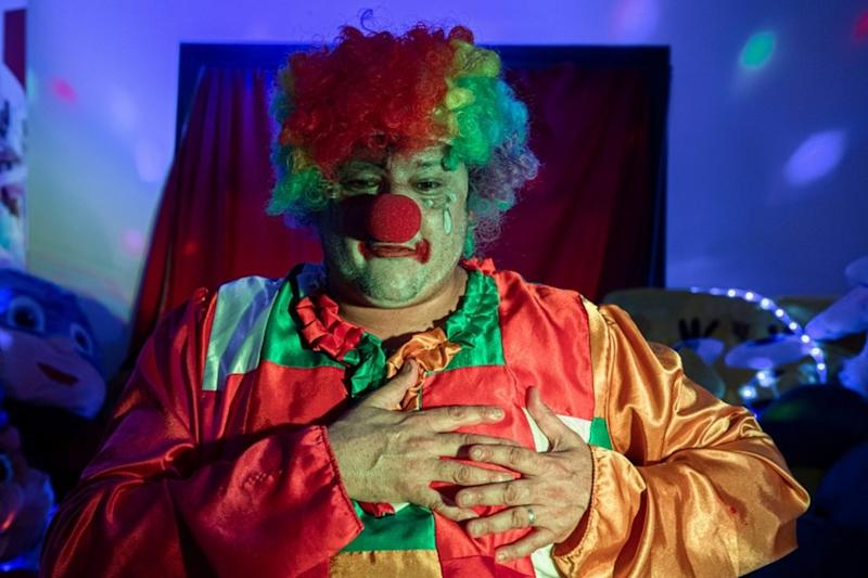 A clown with a painted face, red nose and bright clothing clasps his chest as he mimes a sad expression.
