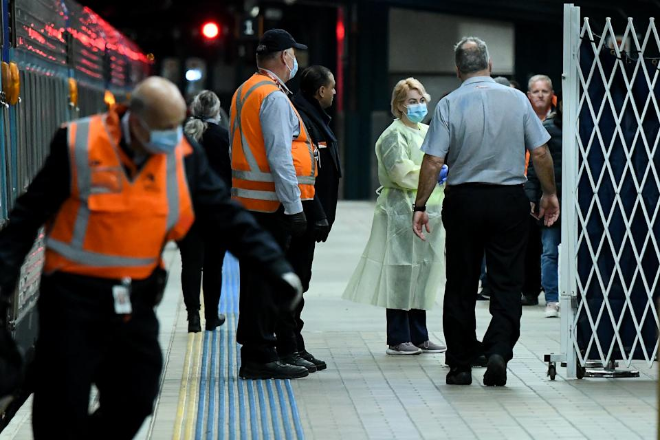 NSW Health officials wearing protective clothing wait for travelers to disembark the XPT Train from Melbourne at Central Station in Sydney, Friday, July 3, 2020. NSW has eased a number of coronavirus restrictions while keeping a wary eye on outbreaks in southern neighbour Victoria. (AAP Image/Bianca De Marchi) NO ARCHIVING