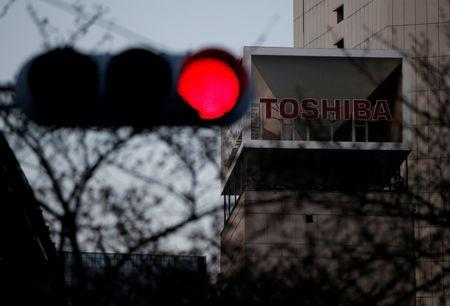 FILE PHOTO The logo of Toshiba Corp is seen behind a traffic light at the company's headquarters in Tokyo, Japan March 29, 2017. REUTERS/Issei Kato/File Photo