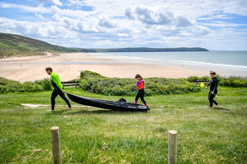 Kyakers wear wetsuits as they make their way towards the beach in Woolacombe, Devon, after the announcement of plans to bring the country out of lockdown.