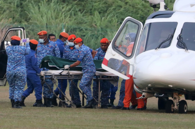 Officials showing loading Nora's body into helicopter after she was found dead in Malaysian jungle.