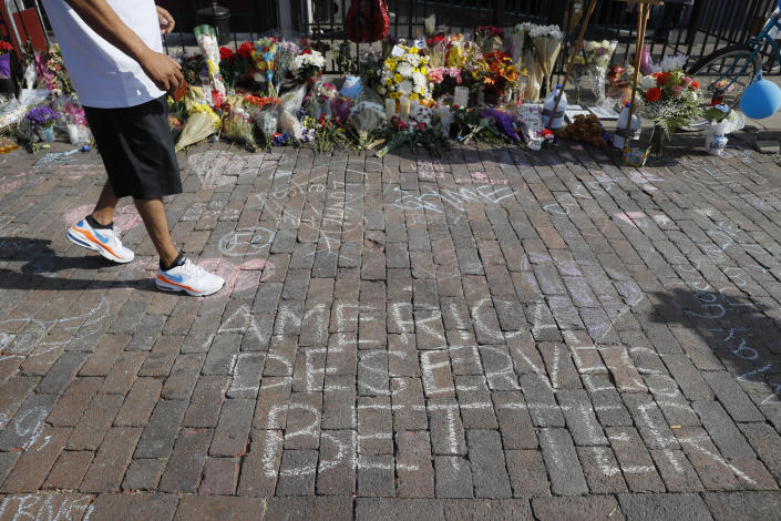 A pedestrian passes a makeshift memorial for the slain and injured victims of Sunday's mass shooting, Aug. 7, 2019, in Dayton, Ohio. (Photo: John Minchillo/AP)