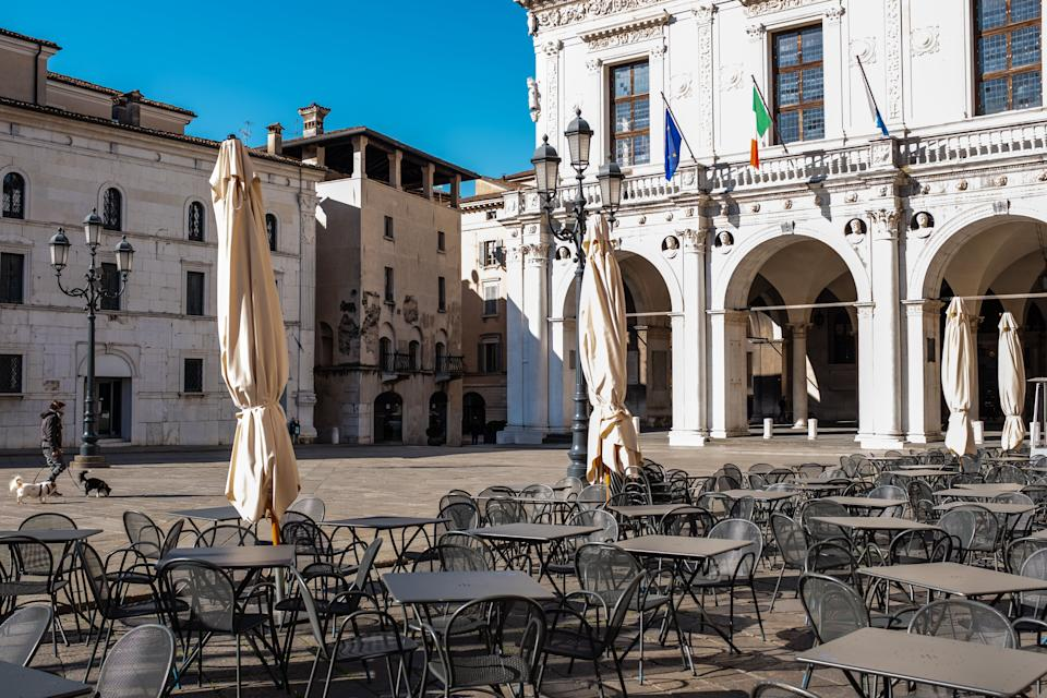 Young adult man wearing a mask walks with his dogs in an empty city. The bar tables are empty in the main square, despite the beautiful day. People are forbidden to gather in public after the government's restrictions to limit the spread of coronavirus. (Photo: Riccardo Cirillo via Getty Images)
