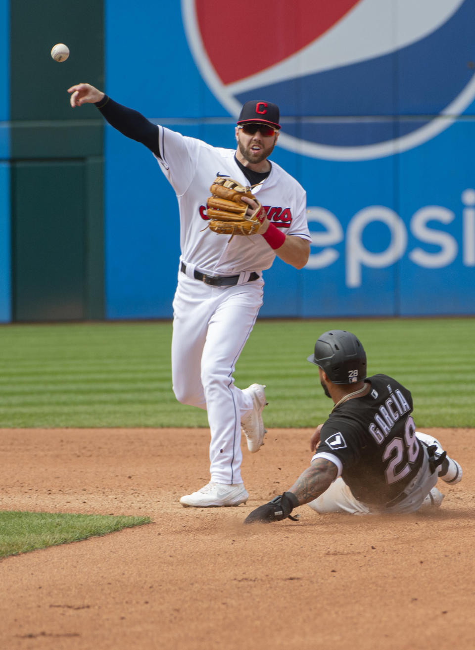 Cleveland Indians' Owen Miller, left, throws to first base to complete a double play after forcing out Chicago White Sox's Leury Garcia, right, at second during the fourth inning of a baseball game in Cleveland, Sunday, Sept. 26, 2021. (AP Photo/Phil Long)