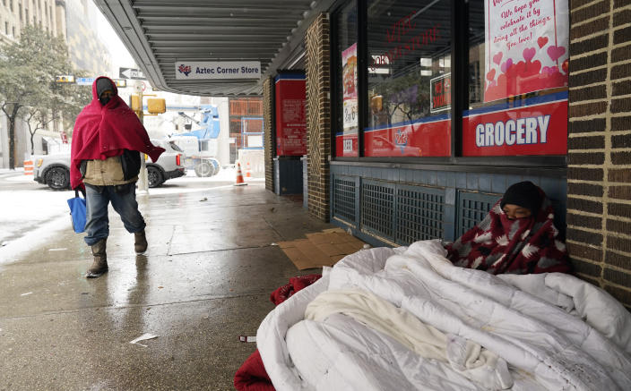 A woman living on the streets uses blankets to keep warm, Thursday, Feb. 18, 2021, in downtown San Antonio. Snow, ice and sub-freezing weather continue to wreak havoc on the state's power grid and utilities. (AP Photo/Eric Gay)