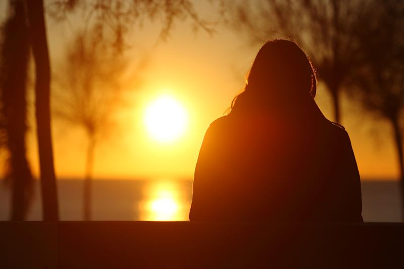 Back view portrait of a silhouette of a lonely woman watching sunset in winter (Photo: AntonioGuillem via Getty Images)