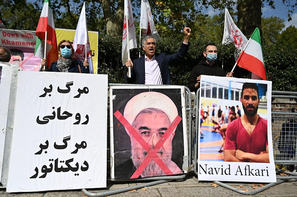 Protesters wave the Lion and Sun flag of the National Council of Resistance of Iran and the white flag of the People's Mujahedin of Iran, two Iranian opposition groups, with a placard depicting the crossed out face of Iran's President Hassan Rouhani as they demonstrate outside the Iranian embassy in London on September 12, 2020 against the execution of Iranian wrestler Navid Afkari in the southern Iranian city of Shiraz and against the Iranian government. - Iran said it executed wrestler Navid Afkari, 27, on September 12, 2020 at a prison in the southern city of Shiraz over the murder of a public sector worker during anti-government protests in August 2018. Reports published abroad say Afkari was condemned on the basis of confessions extracted under torture, prompting online campaigns of support for his release. (Photo by JUSTIN TALLIS / AFP) (Photo by JUSTIN TALLIS/AFP via Getty Images)