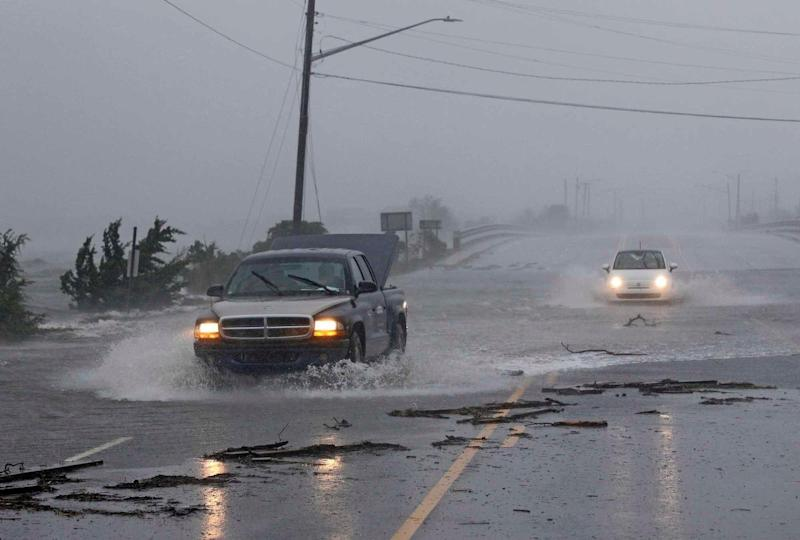 Vehicles drive through water from the White Oak River flooding Highway 24 as Hurricane Florence hit Swansboro, North Carolina on Friday.