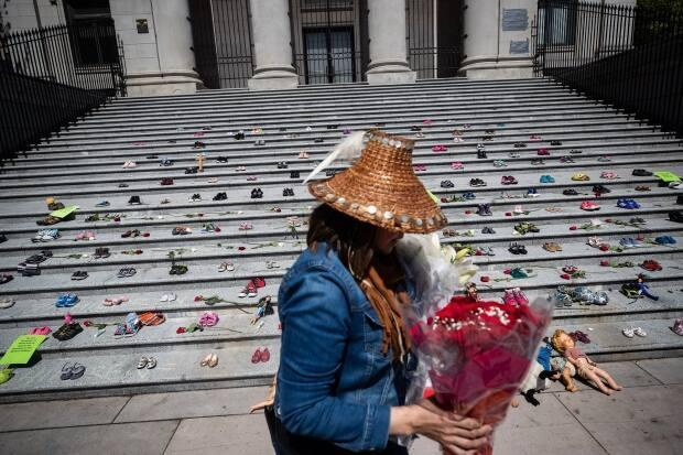 A woman carries flowers on May 28, 2021 to be placed with 215 pairs of children's shoes on the steps of the Vancouver Art Gallery as a memorial to the preliminary discovery of the remains of 215 children found buried at the site of a former residential school in Kamloops.