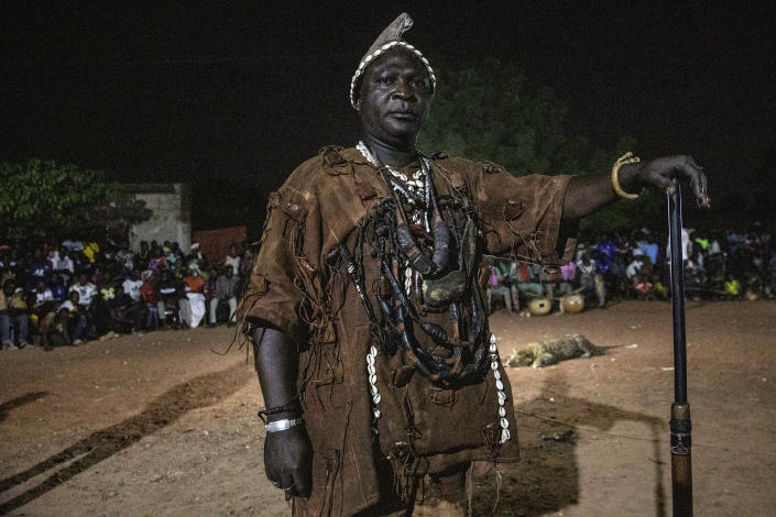 """Idrissa Cisse, a member of the Association of Dozos of Dafra, ancient hunters who have been drawn into the Islamic extremist fight, stands for a portrait during a celebration of their culture in Bobo-Dioulasso, Burkina Faso, 360 kilometers (220 miles) west of the capital, Ouagadougou, on Sunday, March 28, 2021. Cisse says he wouldn't be able to help the army fight extremists without the ancestral powers he says make him bulletproof. """"When we go into the bush, our ancestors give us their goodwill and we go to fight, to do what we have to do."""" (AP Photo/Sophie Garcia)"""
