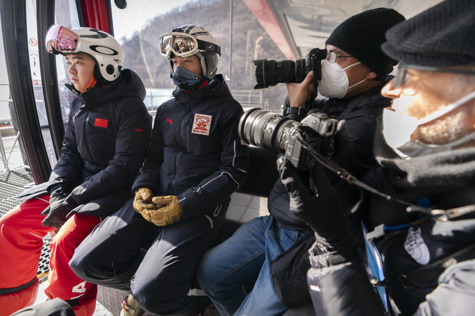 Photographers take photos of skiers as they ride in a gondola at the National Alpine Skiing Center in Yanqing on the outskirts of Beijing, Friday, Feb. 5, 2021. Beijing Olympic organizers showed off the downhill skiing venue and the world's longest bobsled and luge track Friday, one year ahead of the scheduled opening of the 2022 Olympic Winter Games. (AP Photo/Mark Schiefelbein)