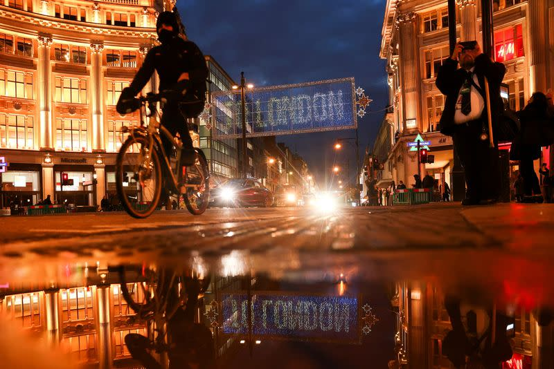 A cyclist moves cycles past the Christmas lights on Oxford Street amid the coronavirus disease (COVID-19) outbreak in London